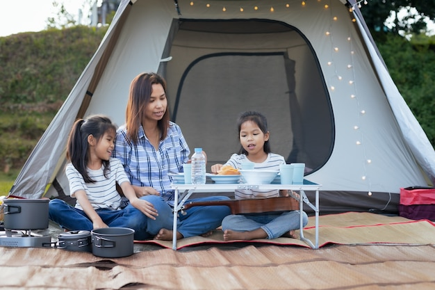 Asiatische mutter und zwei mädchen, die spaß haben, außerhalb des zeltes auf dem campingplatz in der schönen natur zu picknicken.