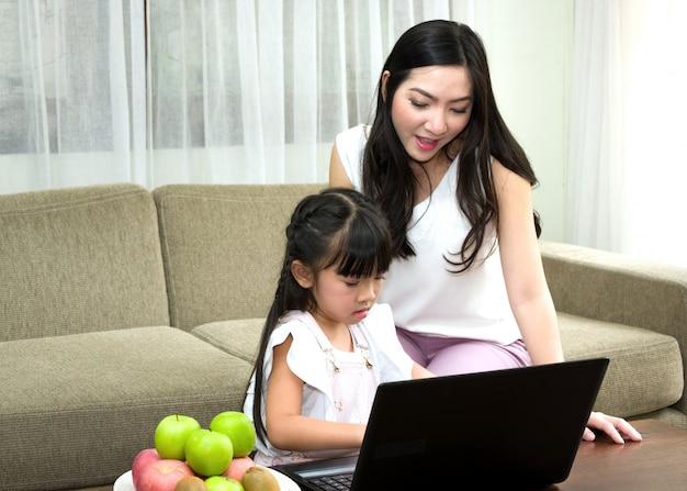 Asiatische mutter unterrichtet ihre tochter, die tastatur auf zu schreiben