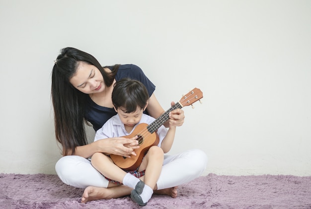 Asiatische mutter unterrichtet ihren sohn, ukulele auf teppich zu spielen