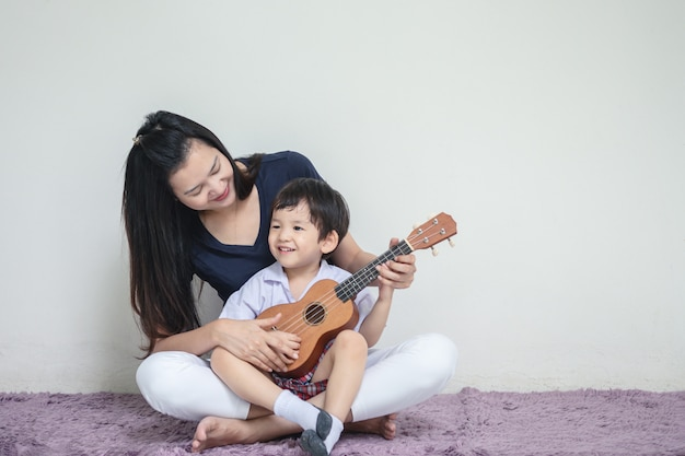 Asiatische mutter unterrichtet ihren sohn, ukulele zu spielen