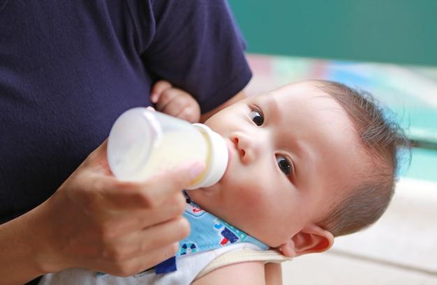 Asiatische neugeborene trinkmilch der nahaufnahme von der flasche durch mutter.