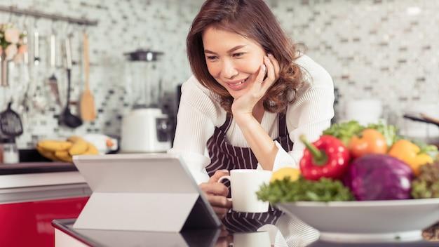 Asiatische niedliche frau mittleren alters, die kaffeetasse hält und tablet-computer mit internet in der küche mit einem lächelnden gesicht und glücklicher weise verbindet. konzept für modernen hausfrauenlebensstil.