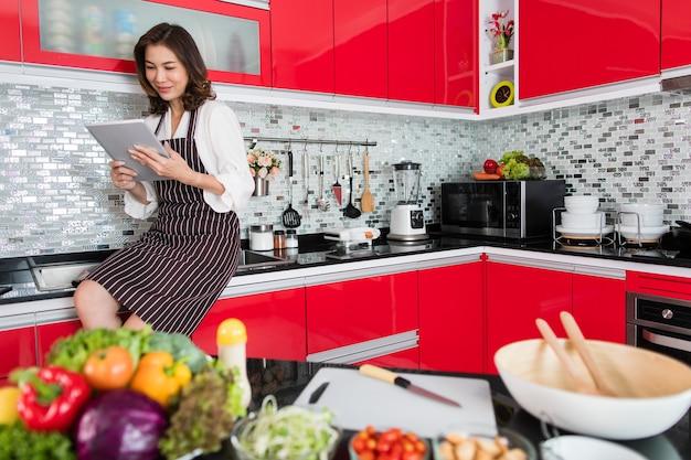 Asiatische niedliche frau mittleren alters in einer schürze, die unter verwendung eines tablet-computers stadiert, verbinden sich mit dem internet in der küche mit einem lächelnden gesicht und einer glücklichen art und weise. konzept für modernen hausfrauenlebensstil.