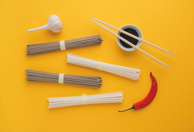 Asiatische nudeln, knoblauch, essstäbchen, roter paprika auf einem hellen gelben hintergrund.