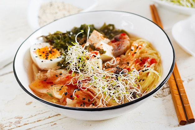 Asiatische nudeln miso ramen mit kohl kimchi, meerespflanze, ei, pilzen und käsetofu in der schüssel auf weißem holztisch.