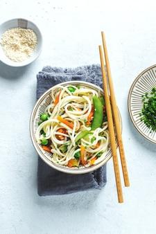 Asiatische nudeln mit gemüse und sesam in schüssel serviert.