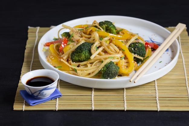 Asiatische nudeln mit gemüse und sojasoße auf bambusmatte und essstäbchen, auf dem schwarzen hintergrund