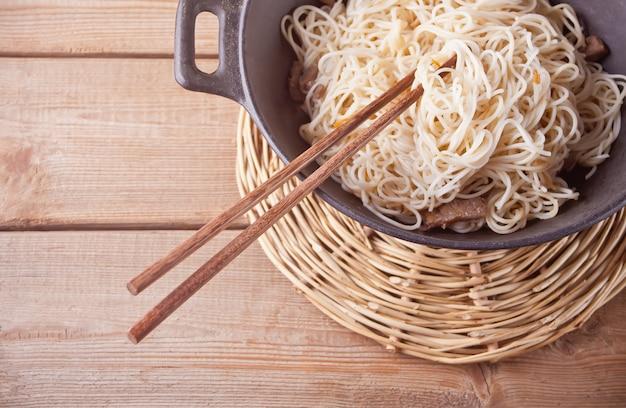 Asiatische nudeln mit rindfleisch, gemüse im wok mit essstäbchen
