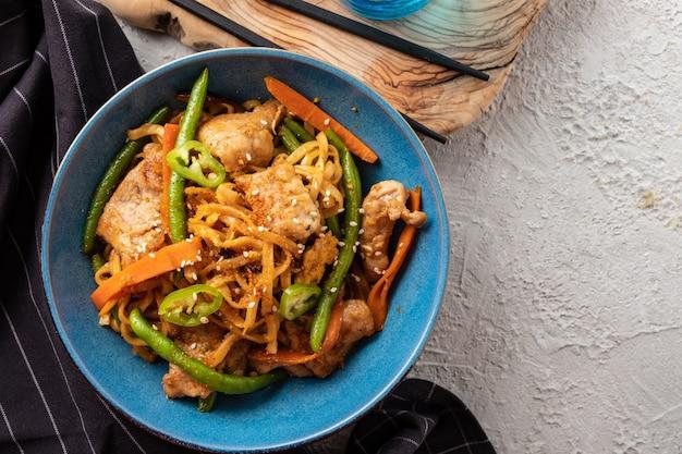 Asiatische nudeln mit schweinefleisch in teriyaki-sauce, mit grünen bohnen, karotten und shiitake-pilzen.