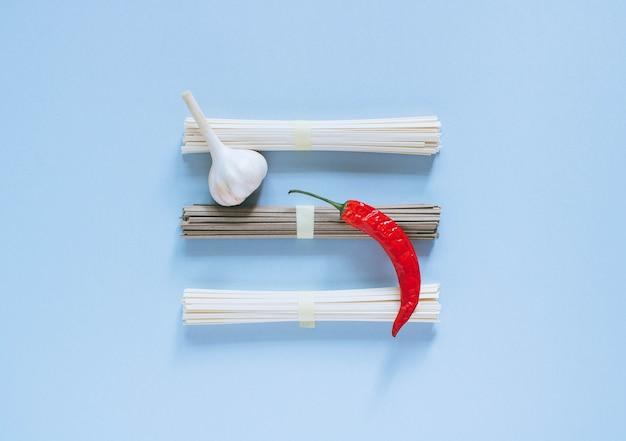 Asiatische nudeln udon und soba, roter paprika, knoblauch auf einem hellen blauen hintergrund.