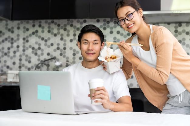 Asiatische paare arbeiten von zu hause in der küche mit lieferung zum mitnehmen