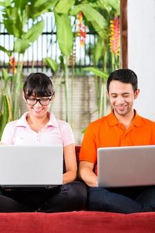 Asiatische paare auf der couch mit einem laptop