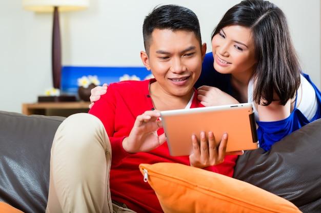 Asiatische paare auf der couch mit einem tabletten-pc