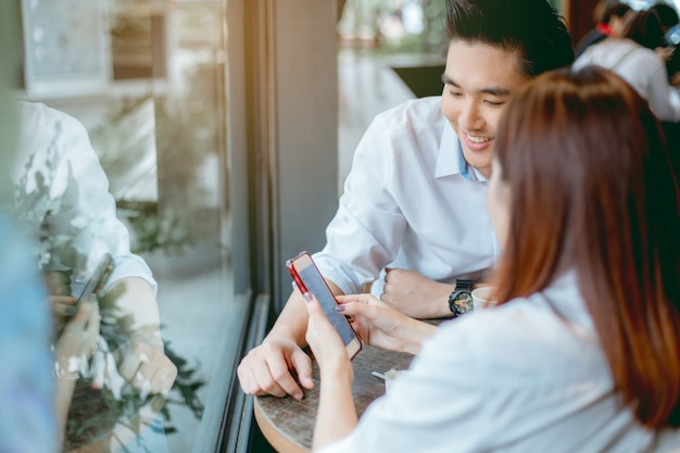 Asiatische paare benutzen smartphones zusammen.