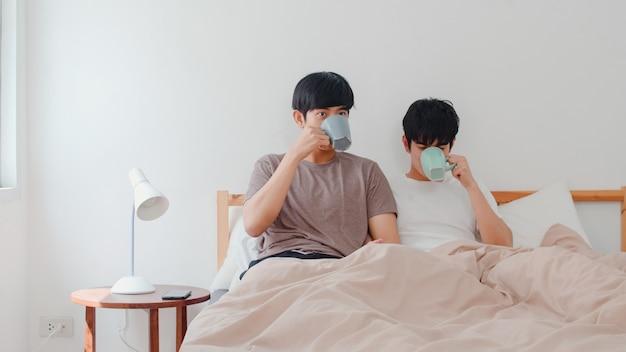 Asiatische paare der homosexuellen männer, die die schöne zeit am modernen haus haben sprechen. das junge glückliche asien-liebhaber lgbtq + mann entspannen sich restgetränkkaffee, nachdem er morgens beim lügen auf bett im schlafzimmer am haus aufgewacht ist.