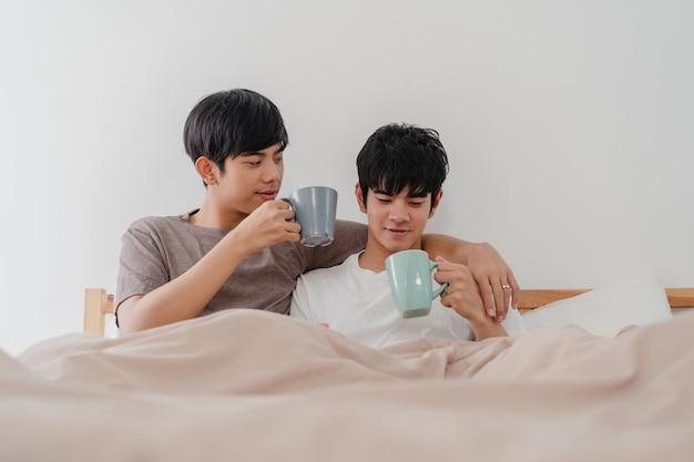 Asiatische paare der homosexuellen männer, die die schöne zeit am modernen haus haben sprechen. das junge glückliche asien-liebhabermann entspannen sich restgetränkkaffee nach wachen beim morgens liegen auf bett im schlafzimmer am haus auf.