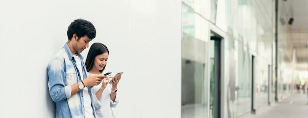 Asiatische paare des glücklichen lächelns unter verwendung des smartphone im kaufhausgehweg