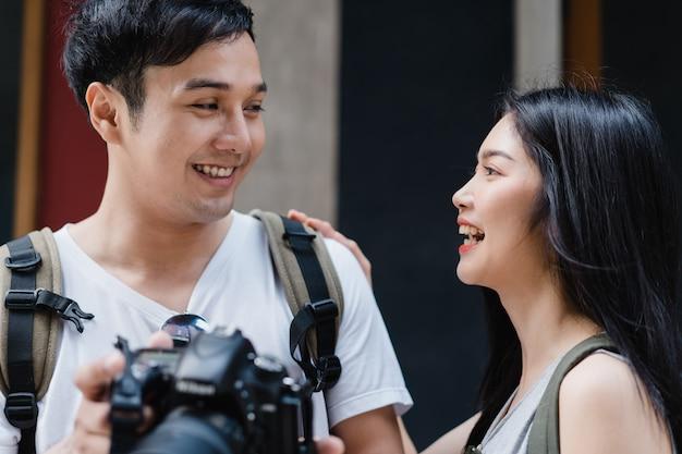 Asiatische paare des reisenden, die kamera für verwenden, machen ein foto, während sie urlaubsreise in peking, china verbringen