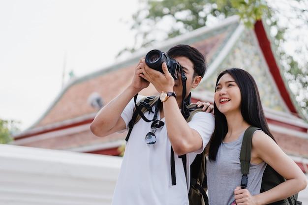 Asiatische paare des reisenden, die kamera für verwenden, machen ein foto, während urlaubsreise in bangkok, thailand verbringen