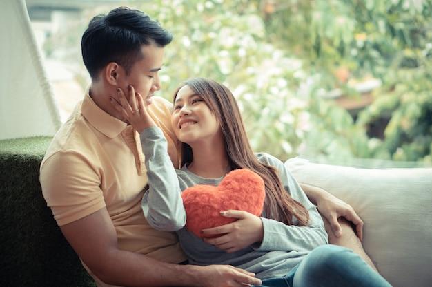 Asiatische paare, die auf dem sofa sitzen, in dem frauen ein rotes herz halten und glücklich lächeln.