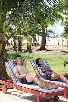 Asiatische paare, die auf ruhesesseln am tropischen erholungsort sich entspannen