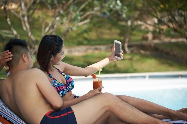 Asiatische paare, die auf ruhesesseln durch swimmingpool liegen und selfies auf smartphone nehmen
