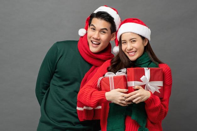 Asiatische paare, die bunte rote und grüne strickjacken mit weihnachtsgeschenkboxen tragen