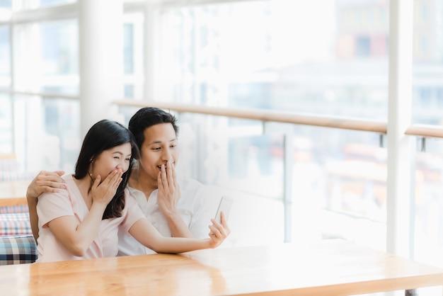 Asiatische paare, die den smartphone betrachten und überraschend
