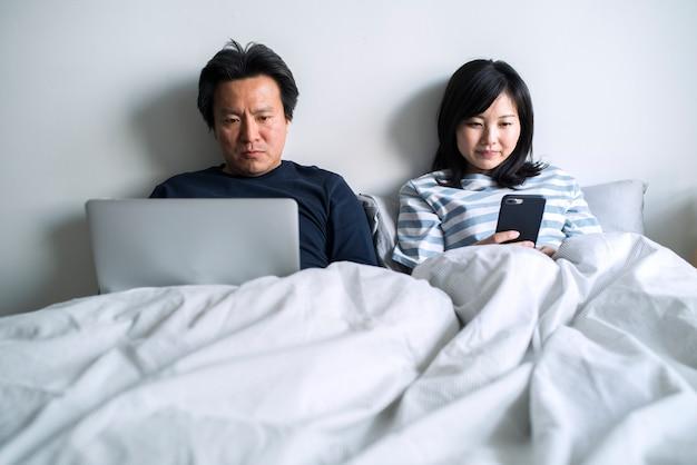 Asiatische paare, die digitale geräte im bett verwenden
