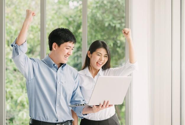 Asiatische paare, die erfolg mit laptop feiern