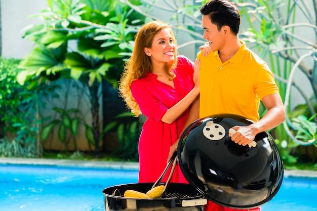 Asiatische paare, die grill am pool haben