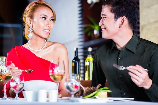 Asiatische paare, die im fantastischen restaurant fein speisen