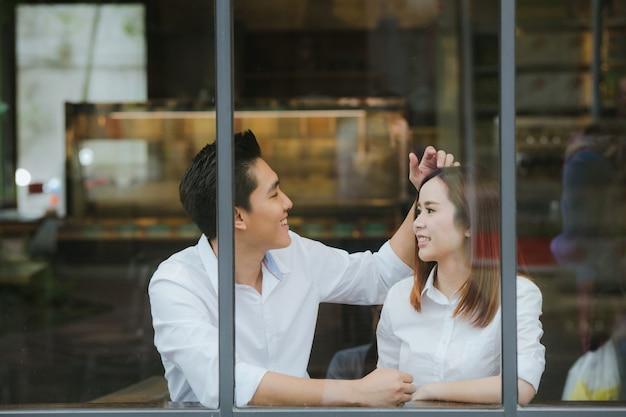 Asiatische paare, die in die liebesdatierung lacht fallen, spaß habend