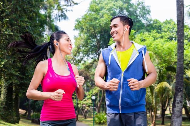 Asiatische paare, die in park für eignung rütteln oder laufen