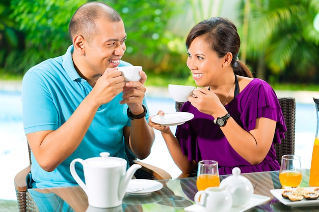 Asiatische paare, die kaffee auf hauptportal trinken