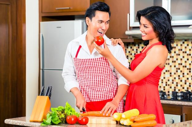 Asiatische paare, die lebensmittel in der inländischen küche zubereiten