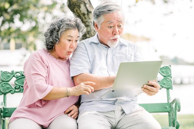 Asiatische paare, die mit laptop überrascht sich fühlen