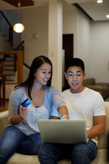 Asiatische paare, die mit laptop und kreditkarte auf couch sitzen und schirm betrachten