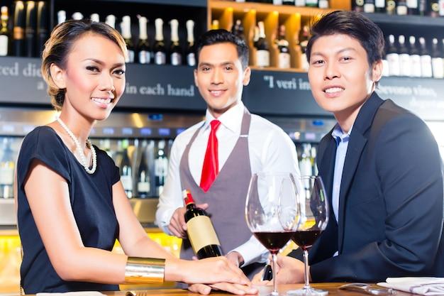 Asiatische paare, die rotwein in der bar schmecken