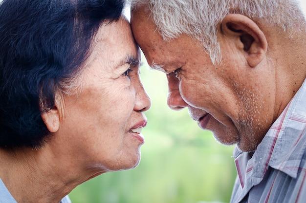 Asiatische paare, die seit über 50 jahren zusammenleben, legen ihre stirn eng zusammen, lächeln und sind glücklich.
