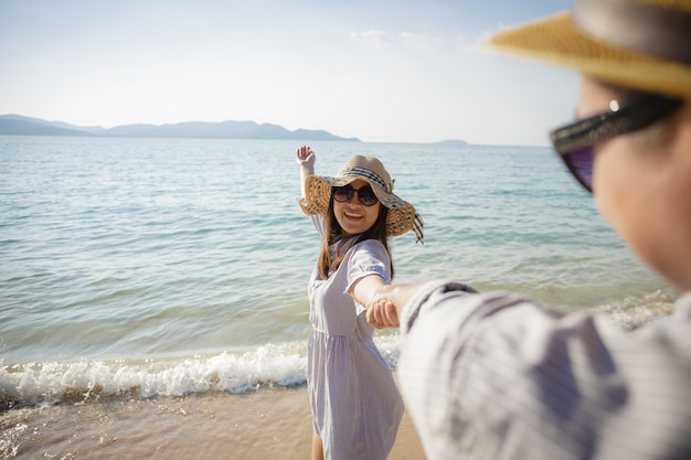 Asiatische paare, die strandferien auf strand, lächelnde freundin geht mit der hand ihres freundes auf dem strand in der sommerzeit halten genießen