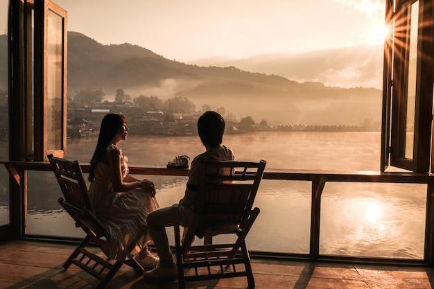 Asiatische paare, die tee-sonnenaufgang bei lee-wein rak thai, chinesische regelung, mae hong son, thailand trinken