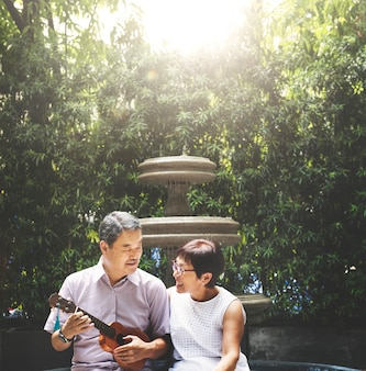 Asiatische paare, die ukulelen-glück-konzept spielen