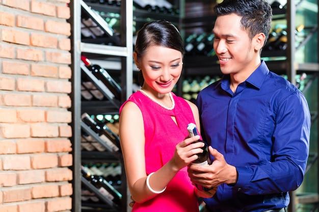 Asiatische paare, die weinflasche im restaurant halten