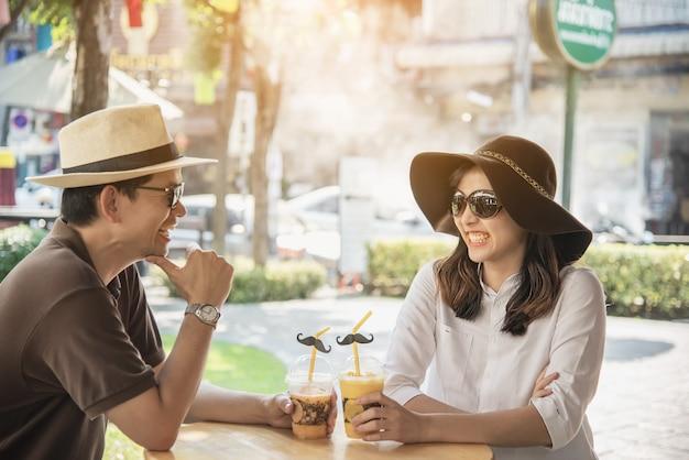 Asiatische paare genießen, an der kaffeestube sitzend zu reisen