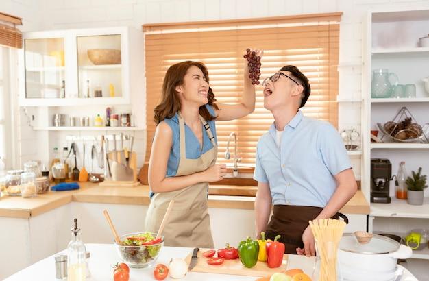 Asiatische paare genießen das gemeinsame kochen von salat im küchenraum zu hause.