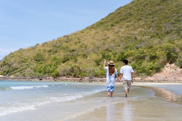 Asiatische paare genießen, entlang den strand zu gehen