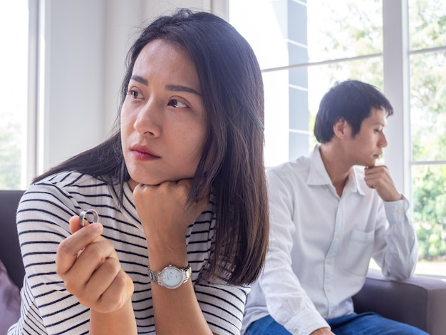 Asiatische paare haben konflikte. die frau nimmt den ehering hinter einem gestressten ehemann und familiären problemen ab.