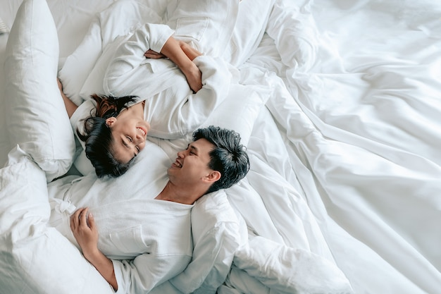 Asiatische paare liegen auf dem bett im schlafzimmer eines modernen hausespaar am valentinstagliebespaar
