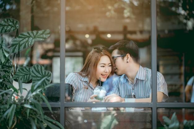 Asiatische paare necken sich glücklich im café.